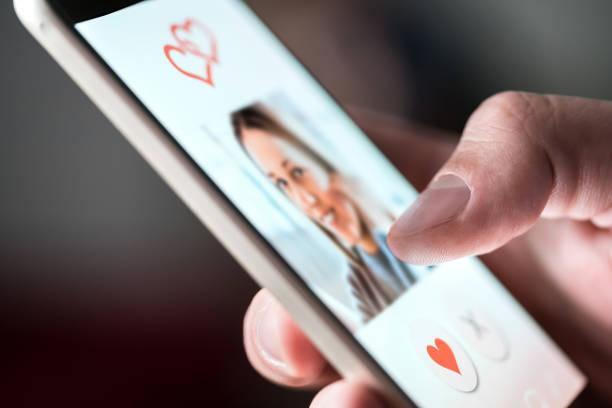 online dating app in smartphone. man kijken naar de foto's voor mooie vrouw. persoon jatten en bevallen van profielen op relatie site of toepassing. één man op zoek naar liefde partner. - daten stockfoto's en -beelden
