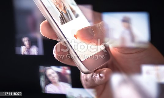 istock Online dating app or site in mobile phone. Finding love and romance from internet with smartphone. Man giving like. Many hologram photos of beautiful woman around cellphone. 1174418079