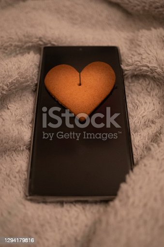 Ginger loved shaped bisquit over a phone symbolising finding love through online dating