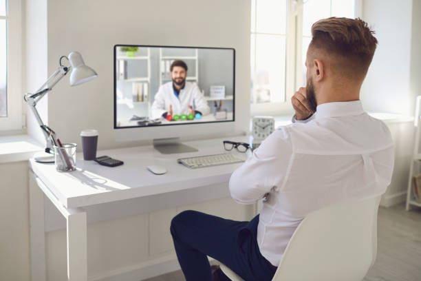 Online doctor.A man talking to a doctor online on a computer on a desk in an office. Online medical consultation. stock photo