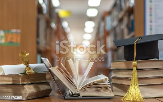 Online education course, E-learning class and e-book digital technology concept with pc computer notebook open in blur school library or classroom background among old stacks of book, textbook
