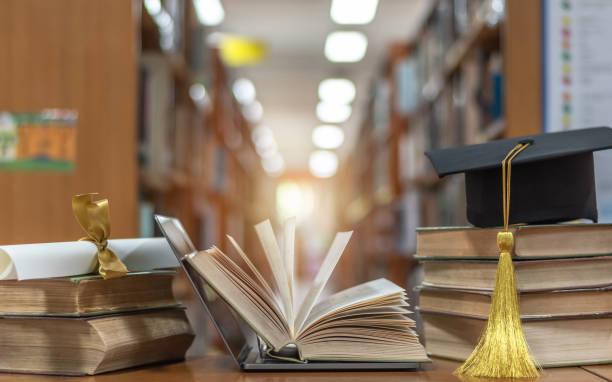 curso de educação online, aula de e-learning e conceito de tecnologia digital de e-book com notebook de computador de computador aberto em biblioteca escolar desfocada ou fundo de sala de aula entre velhas pilhas de livros, livros didáticos - universidade - fotografias e filmes do acervo