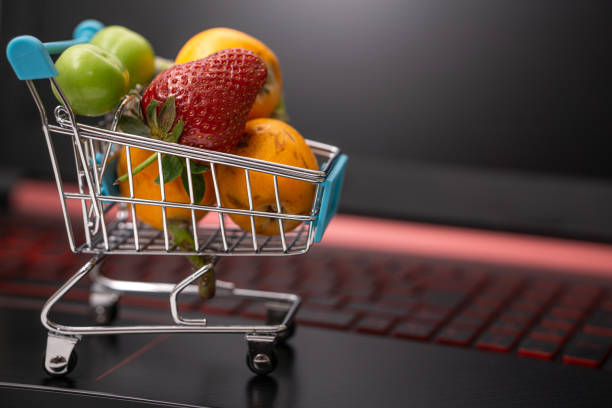 online food and fruit shopping from home with computer stock photo