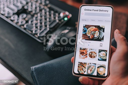 Online food delivery mobile app shown on smart phone screen hold by asian man hands in front of desktop pc