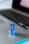 Two blue dices on a laptop. Representing online gambling.