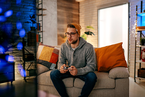 Online gaming concept. Guy playing football video game with joystick