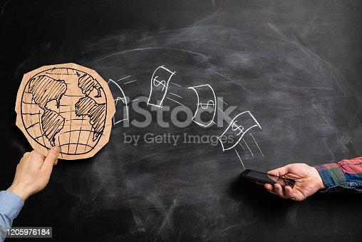 Hand using phone to send money globally