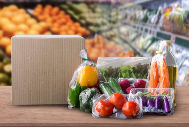 온라인 식료품 개념입니다. 쇼핑 주문 온라인 식품 요리 및 슈퍼마켓 배경 및 도시에서 라이프 스타일에 대 한 음식 배달 서비스에 나무 테이블에 텍스트에 대 한 빈 패키지 상자에 대 한 음식. 스톡 사진