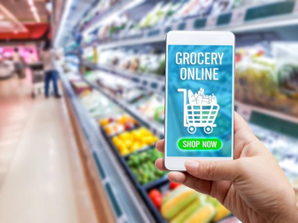 온라인 식료품 쇼핑 개념: 슈퍼마켓 배경에 아이콘 미디어와 함께 화면에 음식을 주문에 대 한 스마트 폰을 들고 여자 손. 도시의 라이프 스타일을 위한 비즈니스 및 기술. 스톡 사진