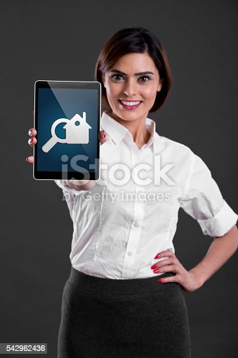 Young businesswoman standing with hand on hip and showing digital tablet. Search for home online concept.