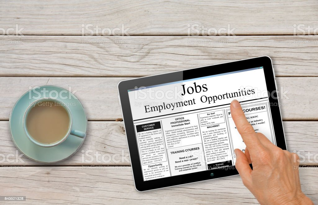 Online job hunting Hand with computer tablet reading employment ads on table with coffee stock photo