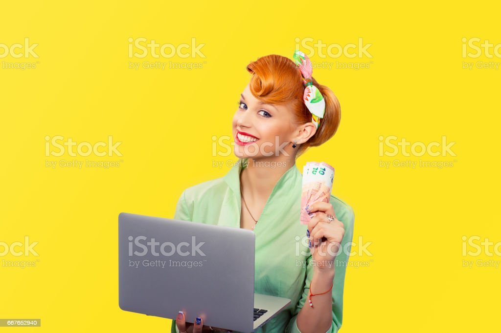 On-line job, internet lottery winner. Closeup red head beautiful young woman girl excited smiling pinup girl green button shirt holding pc and euro bills looking at you camera retro vintage hairstyle stock photo