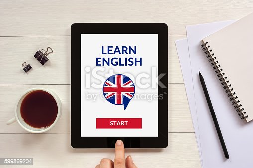 istock Online learn English concept on tablet screen with office objects 599869204