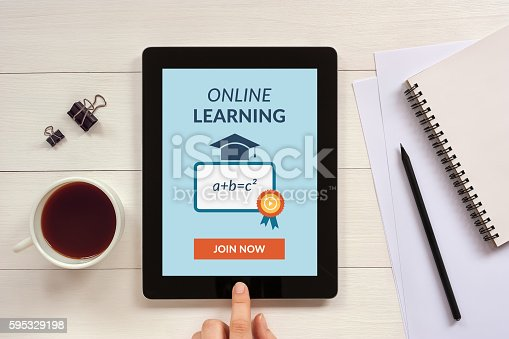 Online learning concept on tablet screen with office objects on white wooden table. All screen content is designed by me.