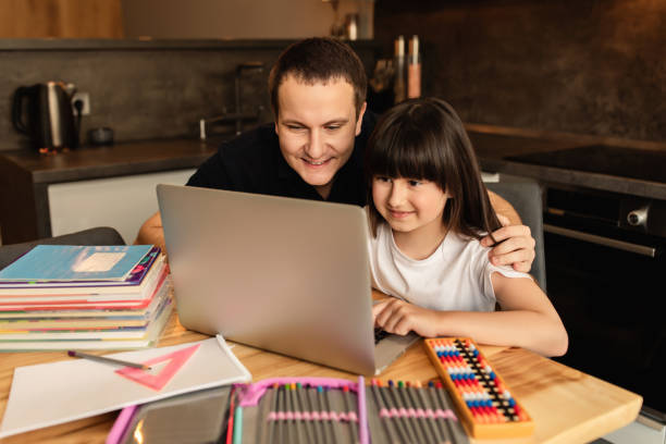 Online learning. Family togetherness while doing homework. Father helps daughter do online lesson at home stock photo