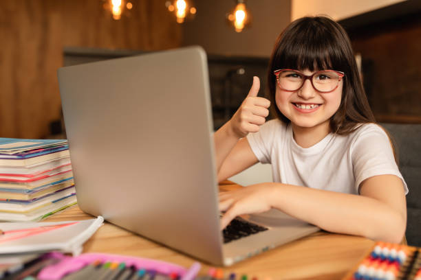 Online learning. Home school. Happy schoolgirl does homework using laptop at home. Online lesson with digital gadget. Distance education, homeschooling stock photo