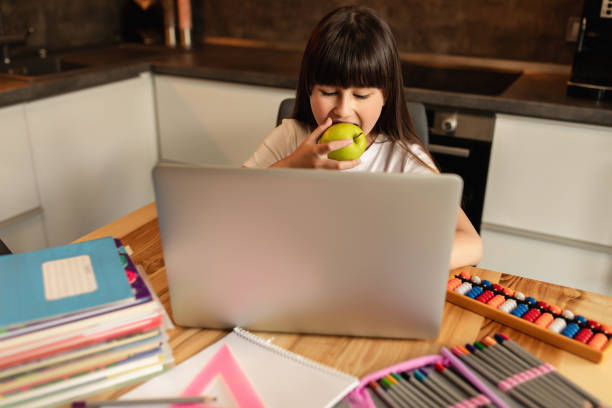 Online learning is good for health. Schoolgirl does homework and eats green apple at home stock photo
