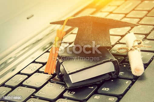 istock online learning or e-learning and online graduate certificate program concept : Black graduation cap, diploma on a laptop computer keyboard, depicts distant learning can be done via cyber / internet 1025416690