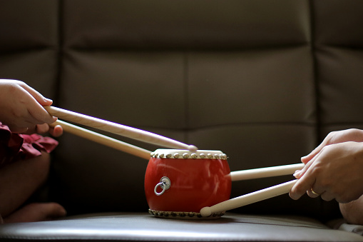 An Asian teenage girl and her brother are practicing drumming using dummy drum at home.