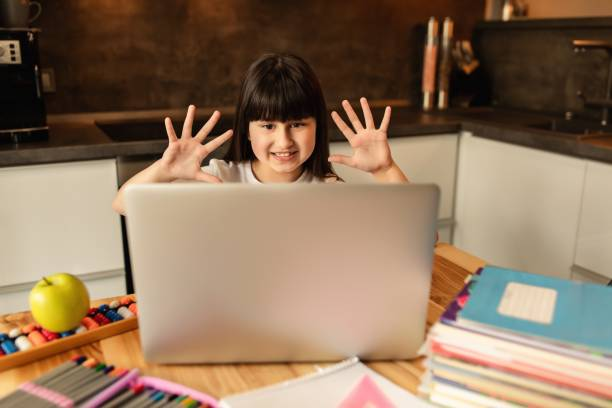 Online learning. Schoolgirl at home, online lesson, video call on laptop. Distance education, home school stock photo