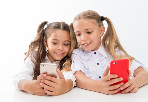 istock Online life concept. Schoolgirls cute pupils use smartphones big diagonal screen to check social networks. Check it out. Send message to friend. Online communication messaging. Game application 1203379543