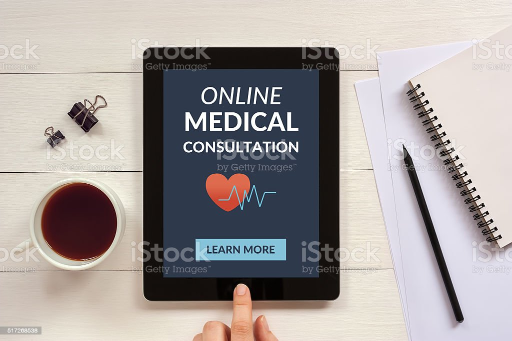 Online medical consultation concept on tablet screen with office objects stock photo
