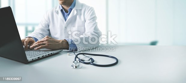 online medical consultation - doctor working on laptop computer in clinic office. copy space
