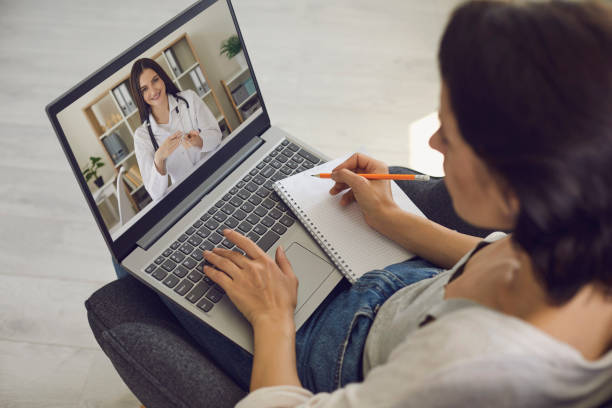 Online medical consultation. The patient consults with the doctor using the video conference application of the medical clinic remotely. Virtual clinic concept. stock photo