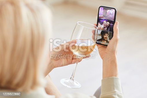 Rear view of woman talking online with her friends on mobile phone and drinking wine they celebrating holiday