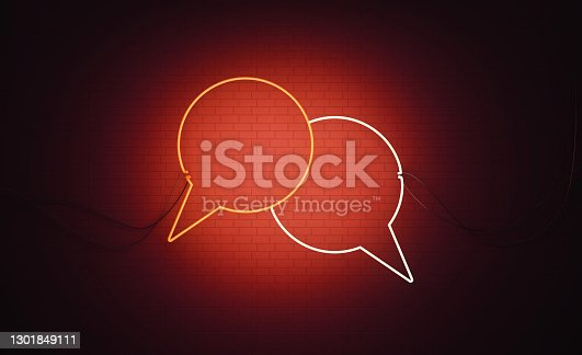 White and red neon speech bubble pair sitting over black wall. Horizontal composition with copy space. Online messaging concept.