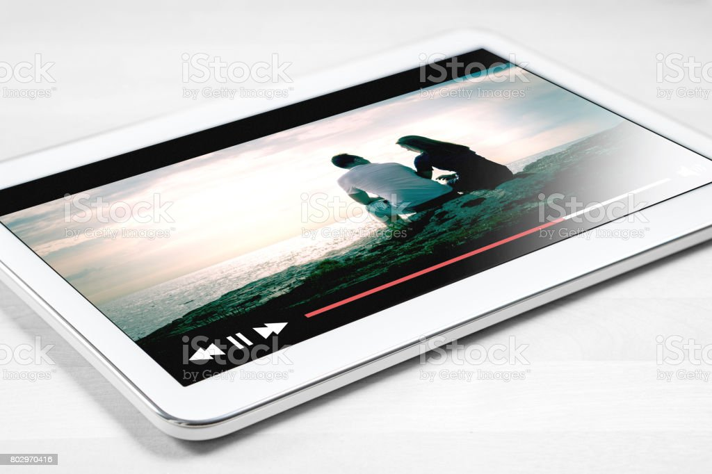 Online movie stream with mobile device. White tablet on wooden table with imaginary video player and film streaming service. stock photo