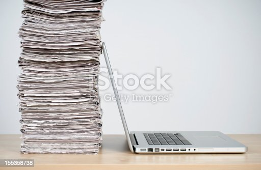 rivalry between old and new: stack of newspapers and laptop computer on the table
