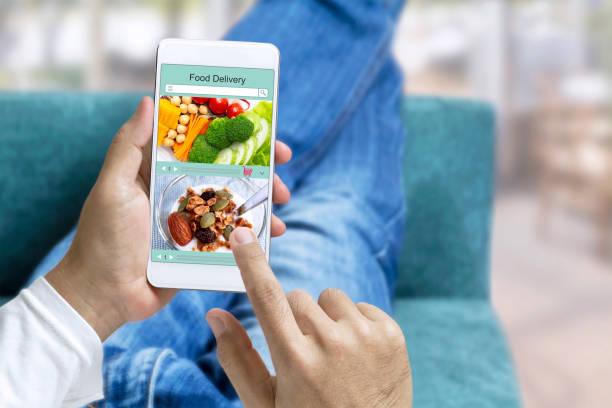 온라인 주문 음식 및 익스프레스 배달 서비스 음식 쇼핑 개념 터치 스크린에 있는 남자의 집에서 소파에 누워 스마트폰을 들고. 도시에서의 라이프 스타일. 스톡 사진