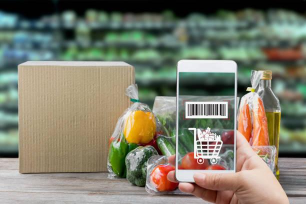 터치 스크린 개념에 온라인 주문 식료품 쇼핑. 손으로 들고 스마트 폰은 재료 및 지불 라벨에 신선한 야채 포장에 바코드를 확인합니다. 기술로 비즈니스. 스톡 사진