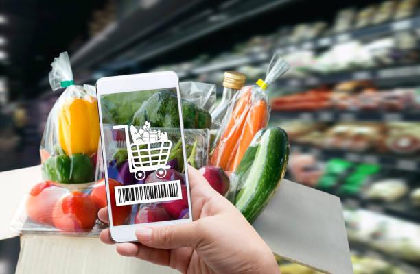 터치 스크린 개념에 온라인 주문 식료품 쇼핑. 성분 및 지불 라벨에 바코드 또는 전자 지갑을 확인 하 고 스마트폰을 들고 있는 여자 손. 라이프 스타일을위한 비즈니스 및 기술. 스톡 사진
