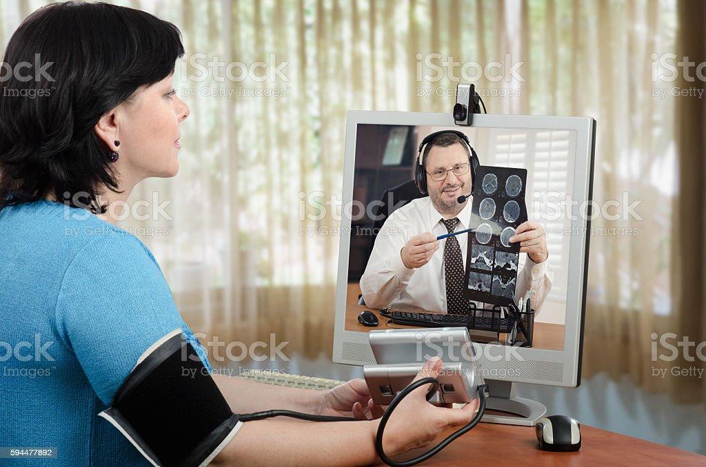 Online patient shows  blood pressure gauge to doctor stock photo