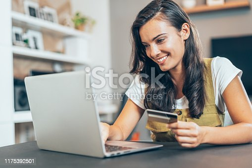Young beautiful woman using credit card and laptop at home