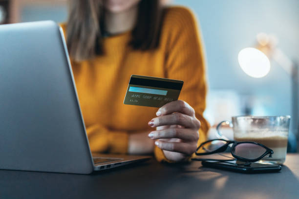 Online payment Unrecognizable person's hand holding credit card in front of lap top at home shopping online stock pictures, royalty-free photos & images