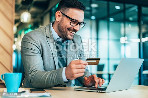 Young smiling businessman using credit card and laptop at modern office