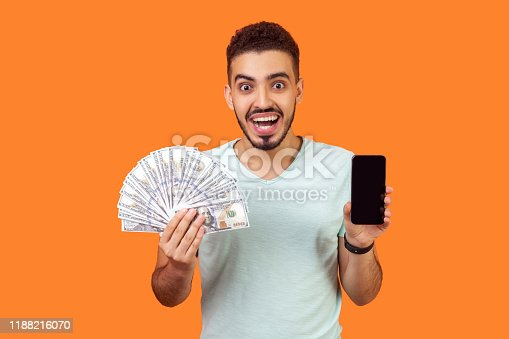 istock Online payment. Portrait of extremely happy man holding money and cellphone. indoor studio shot isolated on orange background 1188216070