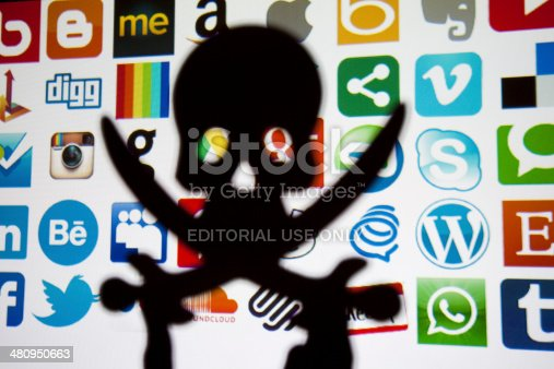 London, United Kingdom - February 17, 2014: Silhouetted skull and crossbones in front of social media and technology logos. Logos include instagram, google plus, Skype,