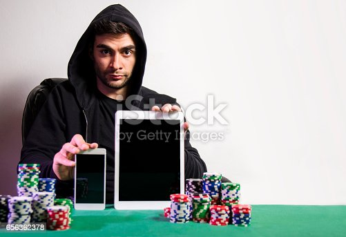 istock Online poker concept, casual man holding smartphone and tablet 656362378