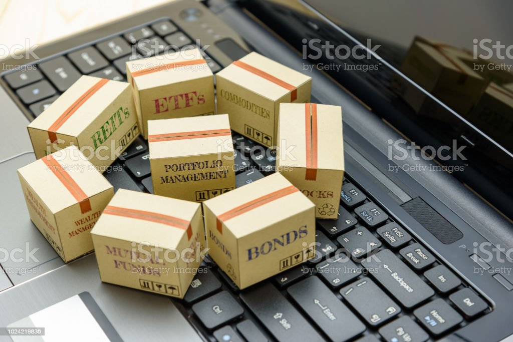 Online portfolio and wealth management with risk diversification concept : Paper boxes of financial instruments i.e ETFs, REITs, stocks, bonds, mutual funds, commodities, on a black laptop keyboard. stock photo