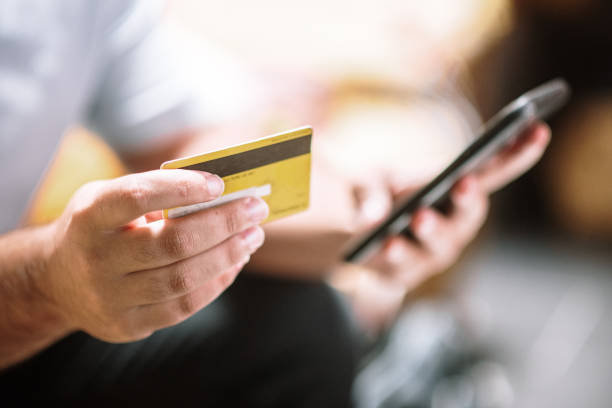 Online purchasing - Hands holding a smart phone and a credit card stock photo