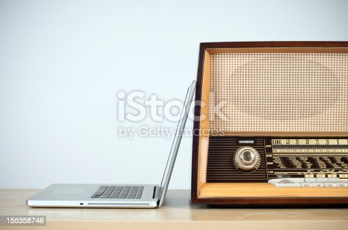 rivalry between old and new:laptop computer and retro radio on the table