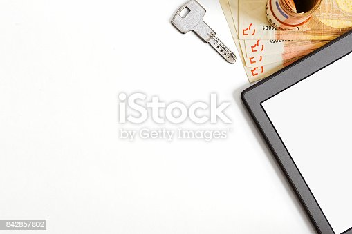 Searching for rental or on sale real estate with a tablet device. Big amount of european union currency papers, tablet with blank screen and a door lock key. Top view with large copyspace.