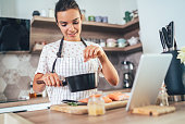 Young beautiful woman using digital tablet while cooking salmon filet in kitchen
