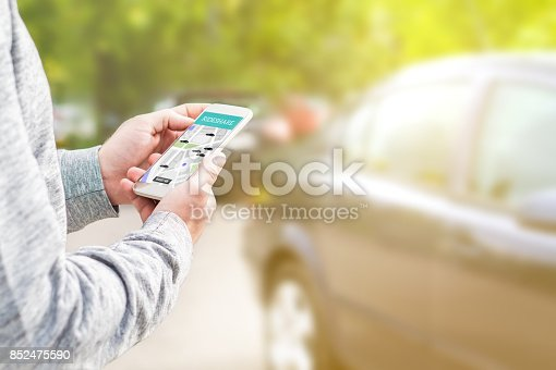 istock Online ride sharing and carpool mobile application. Rideshare taxi app on smartphone screen. Modern people and commuter transportation service. Man holding phone with a car in background. 852475590