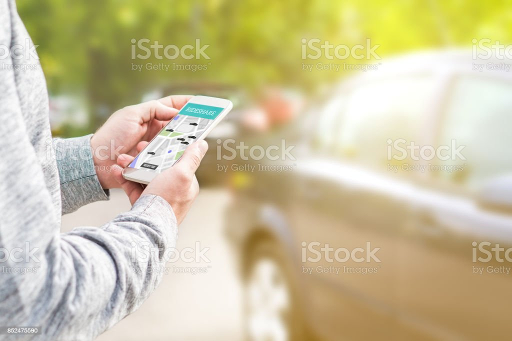 Online ride sharing and carpool mobile application. Rideshare taxi app on smartphone screen. Modern people and commuter transportation service. Man holding phone with a car in background. stock photo