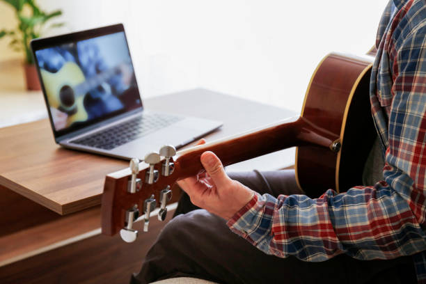 online school of music concept. man learning to lay am acoustic guitar at home. - musicians singers during lockdown foto e immagini stock